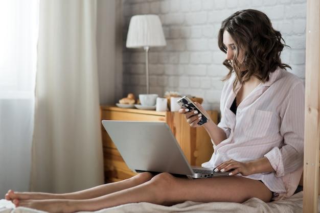 Belle jeune femme blonde dans la chambre sur le lit en lingerie et chemise avec un ordinateur portable