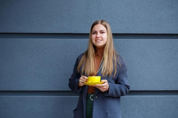 Belle jeune femme blonde dans un manteau gris boit du thé chaud dans une tasse jaune par une froide journée d'automne. délicieuse boisson chaude sur la terrasse du café