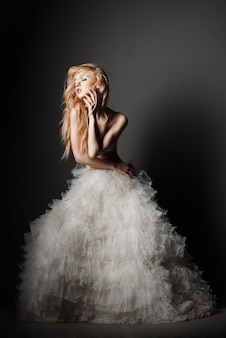 Belle jeune femme blonde dans une pose romantique en jupe blanche