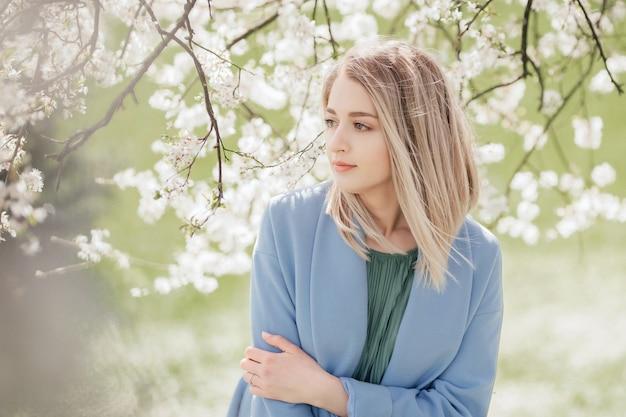 Une belle jeune femme blonde debout près d'un pommier dans une robe verte et un manteau bleu