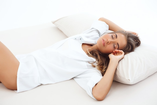 Belle jeune femme blonde dormir sur le lit tôt le matin.