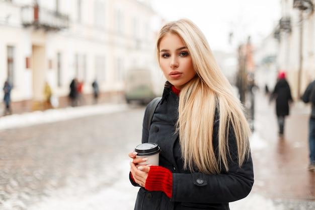 Belle jeune femme blonde avec du café dans un manteau d'hiver de mode dans la ville