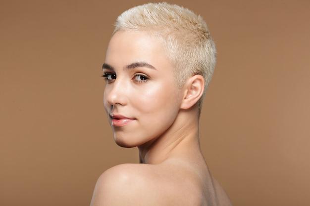 Une belle jeune femme blonde élégante avec une coupe de cheveux courte posant isolée sur un mur beige foncé.