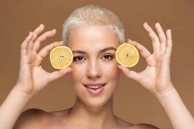 Une belle jeune femme blonde élégante souriante et optimiste avec une coupe de cheveux courte posant isolée sur un mur beige foncé couvrant les yeux avec du citron.