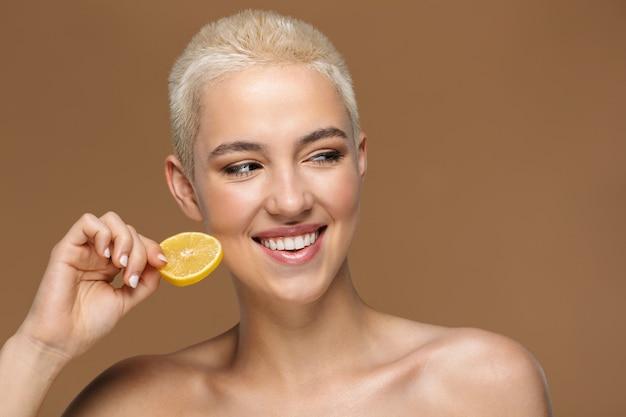 Une belle jeune femme blonde élégante souriante et optimiste avec une coupe de cheveux courte posant isolée sur un mur beige foncé avec du citron.