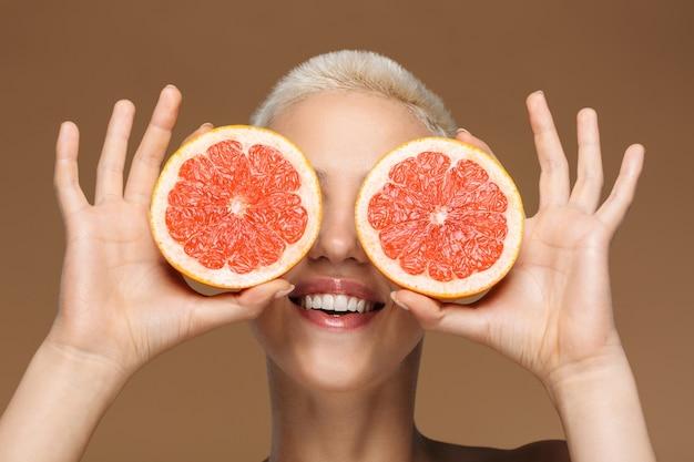 Une belle jeune femme blonde élégante souriante et optimiste avec une coupe de cheveux courte posant isolée sur un mur beige foncé tenant un pamplemousse couvrant les yeux.