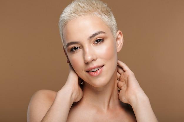 Une belle jeune femme blonde élégante souriante et optimiste avec une coupe de cheveux courte posant isolée sur un mur beige foncé.