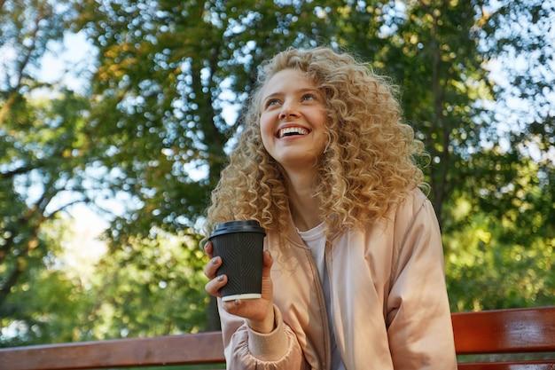 Une belle jeune femme blonde est assise sur un banc de parc, buvant du café