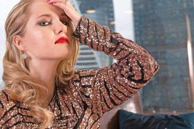 Belle jeune femme blonde est assise sur un canapé en cuir contre la surface d'une fenêtre panoramique donnant sur les gratte-ciel et une grande ville