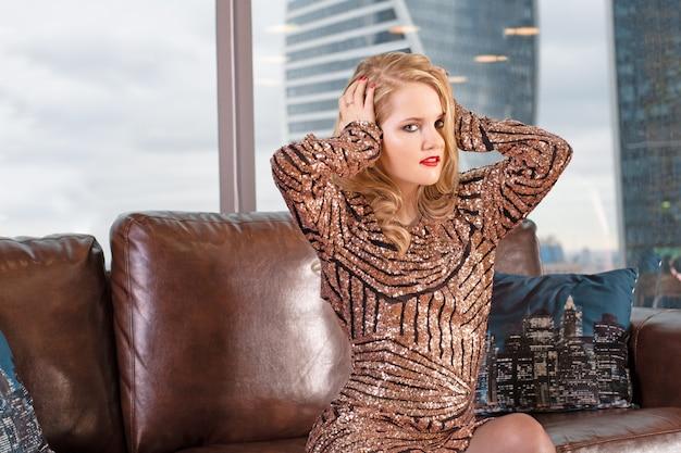 Belle jeune femme blonde est assise sur un canapé en cuir dans le contexte d'une fenêtre panoramique donnant sur les gratte-ciel et une grande ville.