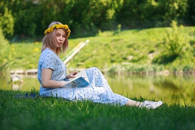 Belle jeune femme blonde étudiant pour ses examens assis sur une herbe près du lac en lisant un livre dans une robe bleu clair. chaleureux. l'été. en plein air.