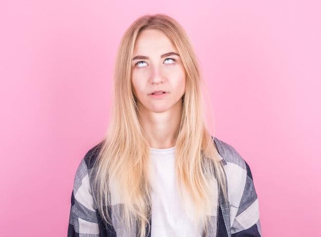 Belle jeune femme blonde européenne sautant sur un fond rose dans une chemise à carreaux