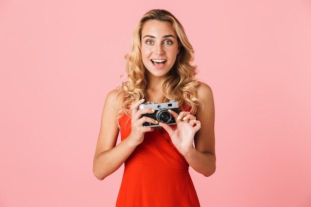 Belle jeune femme blonde excitée vêtue d'une robe d'été isolée sur un mur rose, tenant une caméra portrait