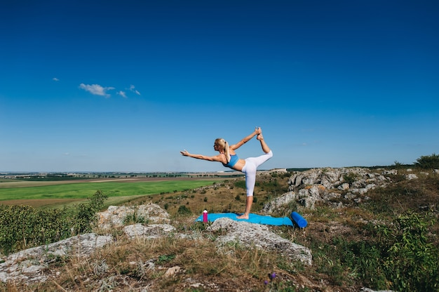 Belle jeune femme blonde, faire des exercices d'yoga sur un rocher. poirier. gymnase et sports de plein air