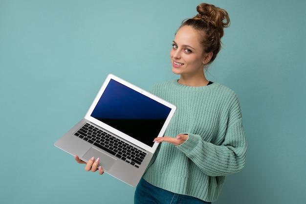 Belle jeune femme blonde foncée aux cheveux bouclés rassemblés regardant la caméra tenant un ordinateur portable avec un écran de moniteur vide avec une maquette et un espace de copie portant une chemise à manches longues bleue isolée sur bleu clair