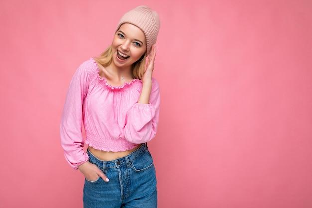 Belle jeune femme blonde heureuse positive isolée sur un mur de fond coloré portant des vêtements décontractés