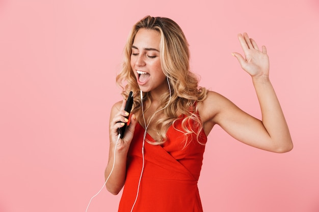 Belle jeune femme blonde joyeuse vêtue d'une robe d'été debout isolée sur un mur rose, écoutant de la musique avec des écouteurs, tenant un téléphone portable, chantant