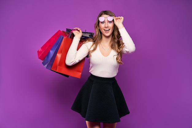 Belle jeune femme blonde à lunettes de soleil tenant des sacs à provisions sur un mur rose