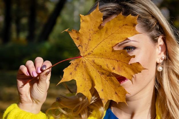 Une belle jeune femme blonde marchant dans le parc en automne et se réjouir des feuilles colorées des arbres.
