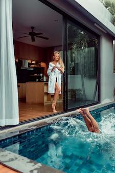 Belle jeune femme blonde en peignoir tenant une tasse de café et regardant quand son homme sautant dans la piscine dans sa villa