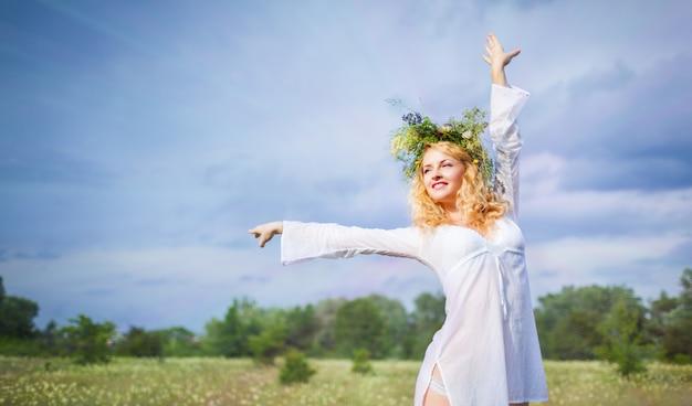 Belle jeune femme blonde en robe blanche et couronne debout avec les yeux fermés et profiter du soleil le jour de l'été