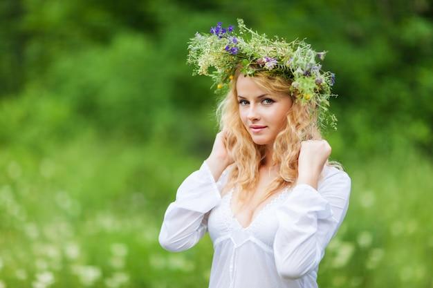 Belle jeune femme blonde en robe blanche et couronne de fleurs debout et regardant la caméra le jour d'été
