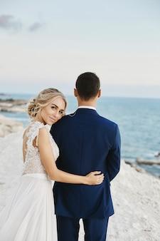 Belle jeune femme blonde en robe de dentelle blanche s'appuie sur le bel homme dans le costume bleu élégant sur le rocher blanc sur la côte de la mer adriatique. fille modèle dans une robe de mariée avec marié élégant