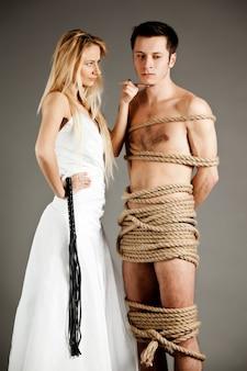 Belle jeune femme blonde en robe de mariée debout près de son homme nu ligoté avec des cordes et tenant des cils en cuir à la main sur un espace gris
