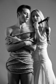 Belle jeune femme blonde en robe de mariée debout près de son homme nu ligoté avec des cordes et tenant des cils en cuir à la main sur fond gris