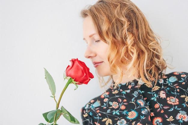 Belle jeune femme blonde en robe avec une rose rouge sur blanc isolée