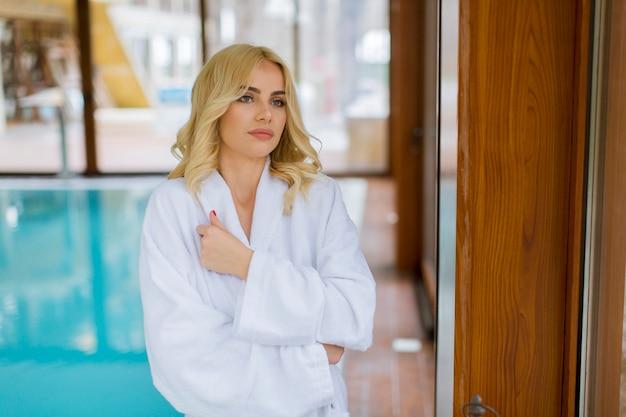Belle jeune femme blonde se détendre à la piscine couverte