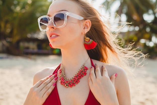 Belle jeune femme blonde se faire bronzer sur la plage en maillot de bain rouge, lunettes de soleil
