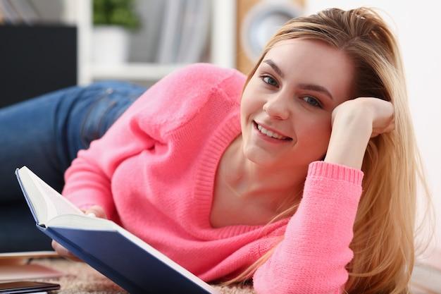 Belle jeune femme blonde se trouvent sur le sol lire le livre