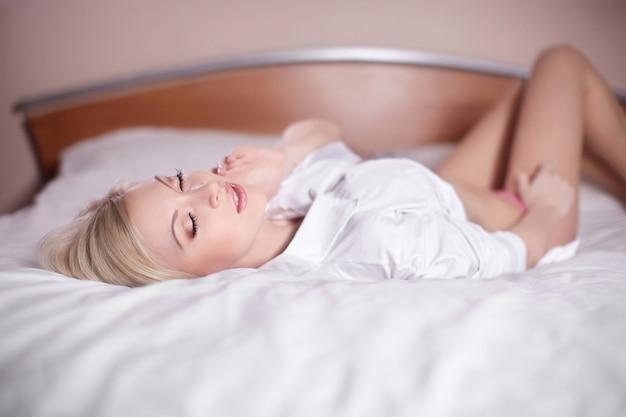 Belle jeune femme blonde sensuelle sexy pose dans son lit nu