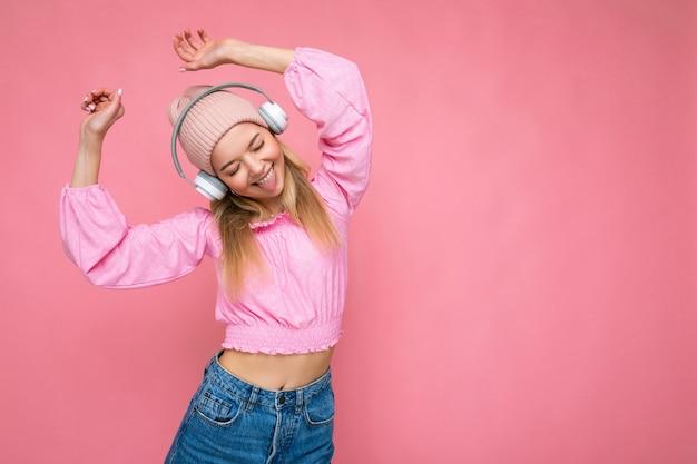 Belle jeune femme blonde souriante et heureuse portant un chemisier rose et un chapeau rose isolé sur rose