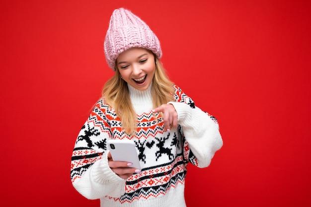 Belle jeune femme blonde souriante portant un bonnet tricoté chaud et un pull chaud d'hiver