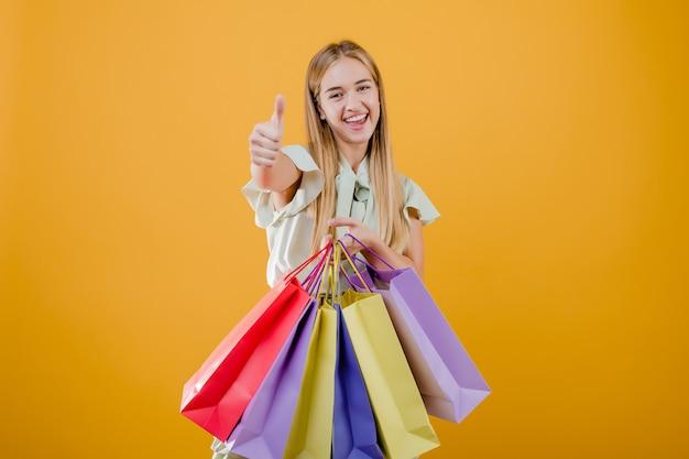Belle jeune femme blonde souriante avec des sacs colorés, isolés sur jaune