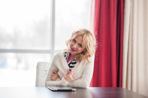 Une belle jeune femme blonde à la table à l'aide d'un ordinateur portable.