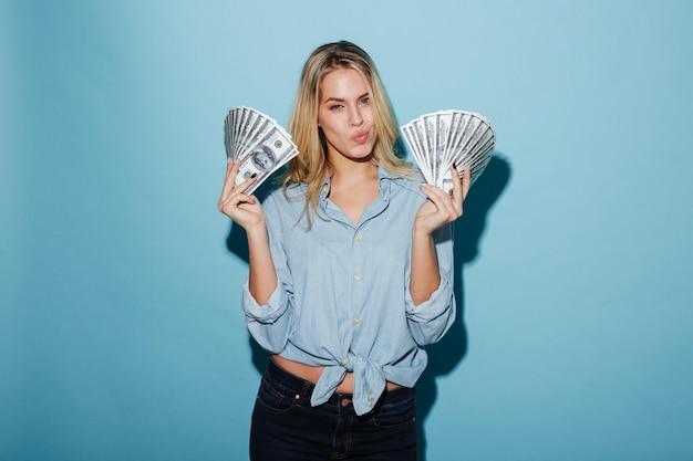 Belle jeune femme blonde tenant de l'argent en mains
