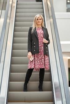 Belle jeune femme blonde vêtue d'une robe sur un escalator dans un centre commercial, avec un téléphone dans ses mains