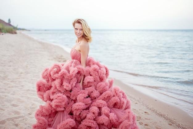 Belle jeune femme blonde vêtue d'une robe rose sur la plage