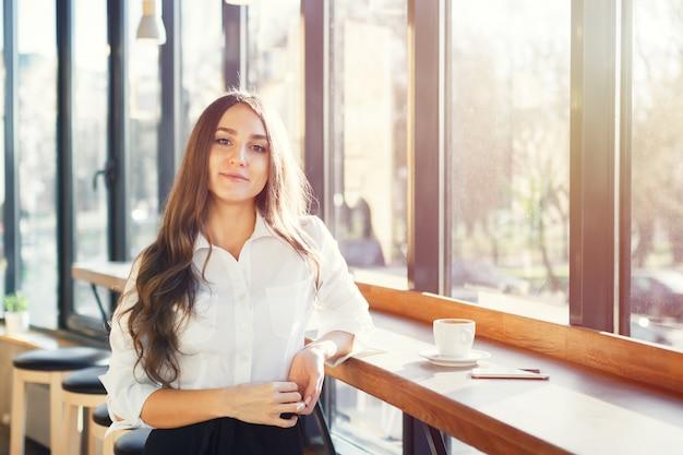 Belle jeune femme en blouse blanche boire du café et à l'aide de smartphone au café