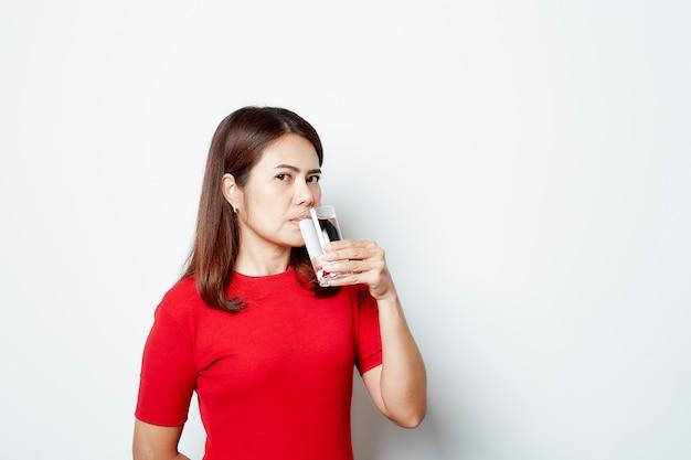 Belle jeune femme boit de l'eau dans un verre