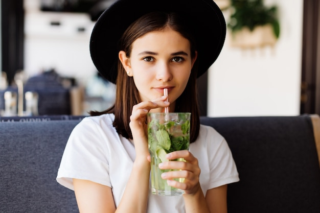 Belle jeune femme boit de la limonade au café