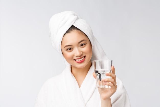 Belle jeune femme en bonne santé l'eau potable, maquillage naturel visage beauté, isolé sur