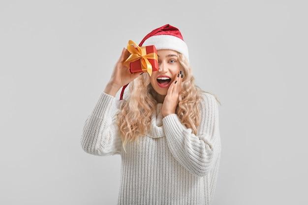 Belle jeune femme en bonnet de noel avec boîte-cadeau sur une surface claire