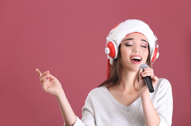 Belle jeune femme en bonnet de noel chantant des chansons de noël sur fond de couleur