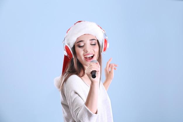 Belle jeune femme en bonnet de noel chantant des chansons de noël