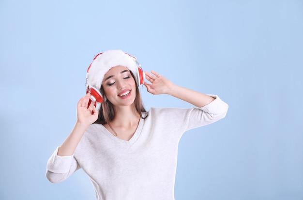 Belle jeune femme en bonnet de noel écoutant de la musique de noël sur fond de couleur