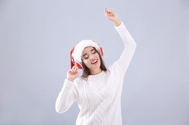 Belle jeune femme en bonnet de noel écoutant de la musique de noël